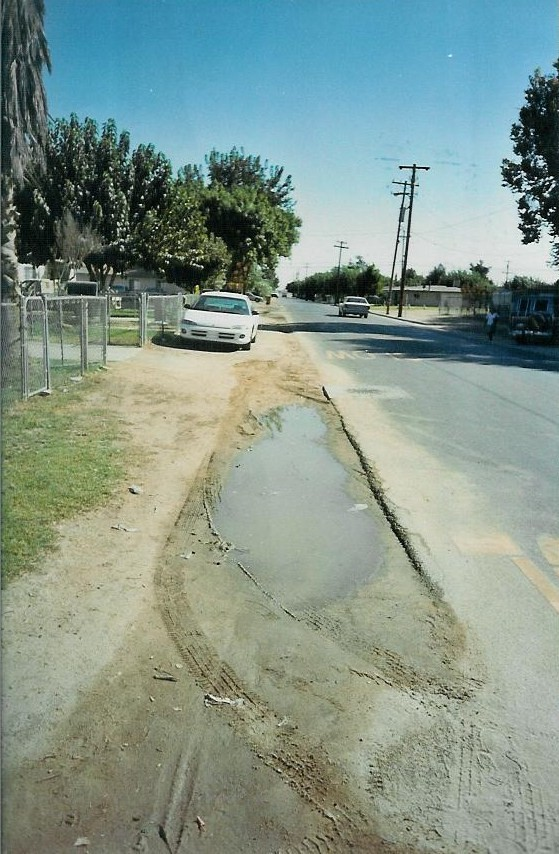 Prior to sidewalk, curb, and gutter installations, Myrtle Avenue in Lamont, CA was frequently muddy or flooded.